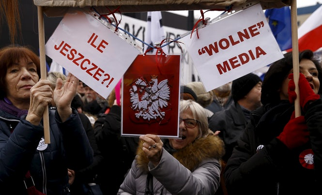 Protesters in Warsaw hold placards that read