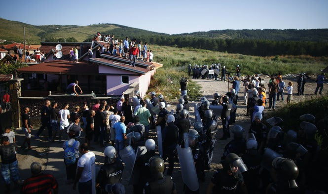 Bulgarian police surround a house as Roma stand on the roof to protest against the demolition of the house in a Roma suburb in the city of Stara Zagora in 2014. (Image: Stoyan Nenov, Reuters)