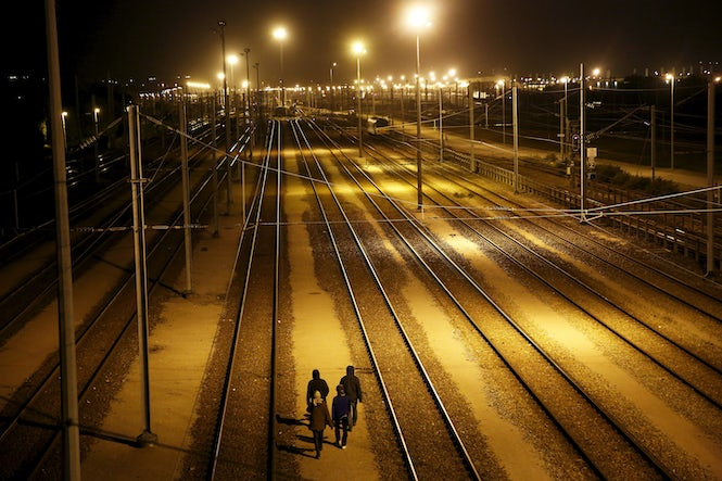 Migrants walk after crossing a fence as they attempt to access the Channel Tunnel in Frethun, near Calais, France. The ECJ case arose from an arrest at the tunnel's entrance. (REUTERS/Juan Medina)