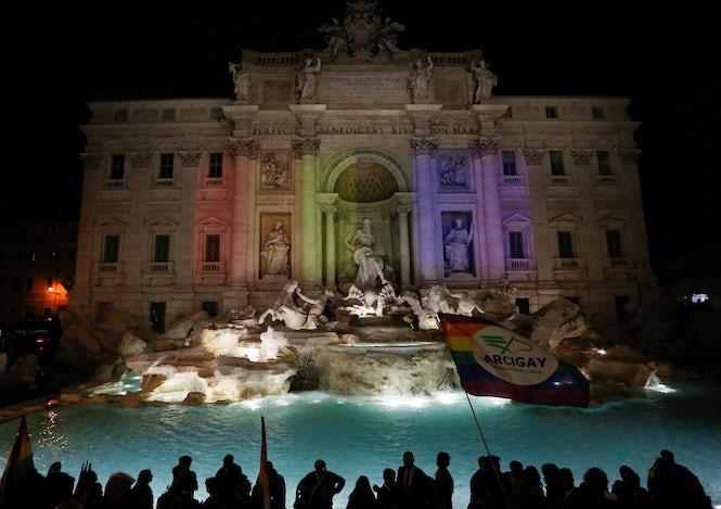 Proyección de luces arcoiris en la Fontana de Trevi para celebrar la ley de uniones civiles en Roma el 11 de mayo de 2016. (REUTERS/Alessandro Bianchi)