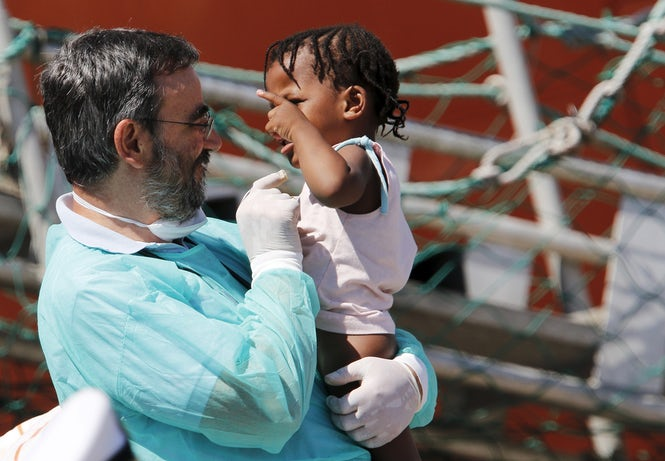 A doctor carries a migrant child as they disembark in Catania, Italy, in August 2015. Protections for unaccompanied foreign minors are still lacking in Italy. (REUTERS/Antonio Parrinello)