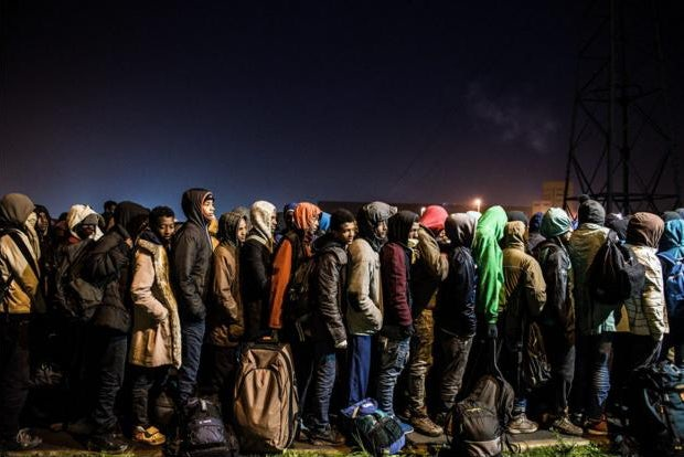 Migrants wait in line to be bussed away to migrant centers across France.  (Image: Sara Prestianni)