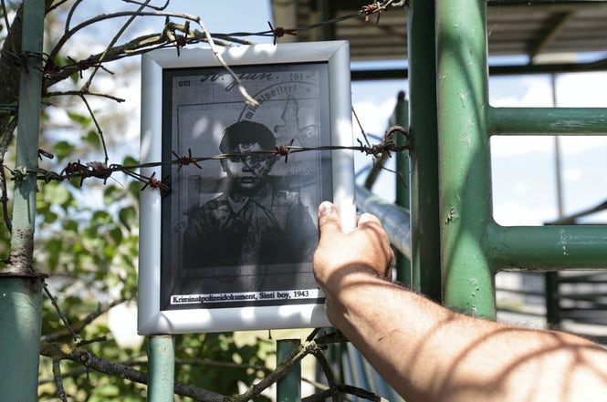 A man places a picture of a Roma victim of the Holocaust on the fence of the pig farm at the Lety concentration camp site.  (REUTERS/David W Cerny)