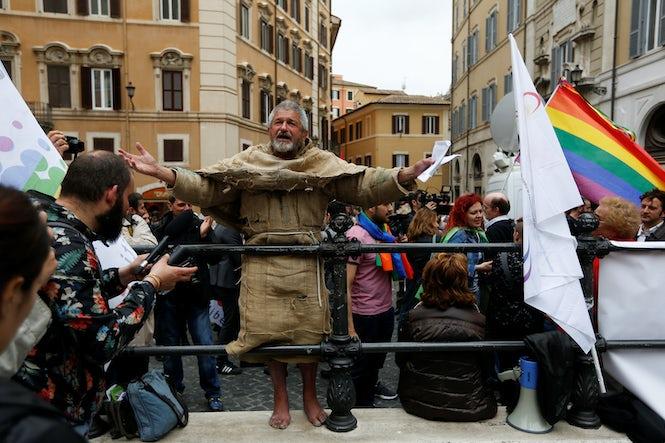 Vyras protestuoja priešais Italijos Parlamenta, kuria tuo metu vyksta balsavimas dėl civilinių santuokų įstatymo. Pastarasis susilaukė kritikos ir iš LGBTI teisių aktyvistų, ir iš jų priešininkų. (REUTERS/Alessandro Bianchi)