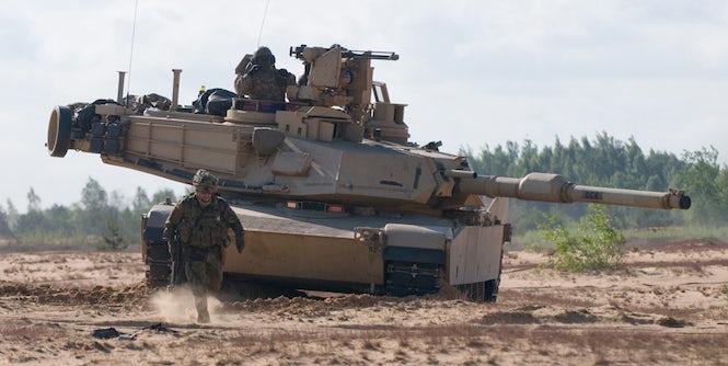 Vasarą vykusių pratybų metu Ruklos stovyklos teritorijoje rieda tankas. Tai, kad netolimais randasi karinės pajėgos, primena daugeliui migrantų apie karą, nuo kurio jie ir bėgo.  (Nuotrauka: Army Europe Images)