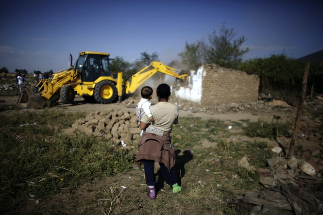 A Bulgarian Roma woman holds a child as they watch an excavator demolish a house in a Roma village in Bulgaria in 2012. (Image: Stoyan Nenov, Reuters)