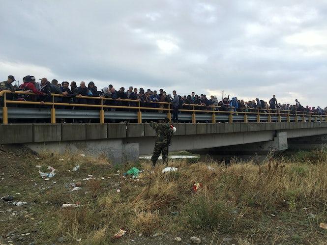 Vluchtelingen op een weg in Macedoniè worden tegengehouden om verder te reizen. (Beeld: Seth Frantzman)